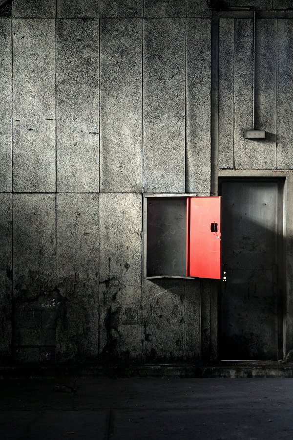 Red box on a grey wall, in an abandoned factory in France de LeLuxographe